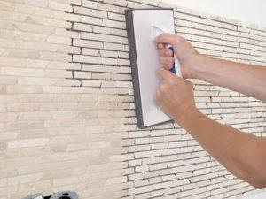 Artisan pose de mur en pierre