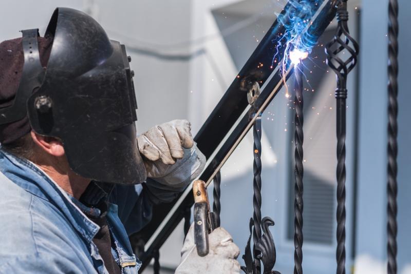Ferronnier travaillant une structure en fer forgé