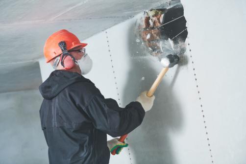 Demolition d'une cloison a l'aide d'un marteau