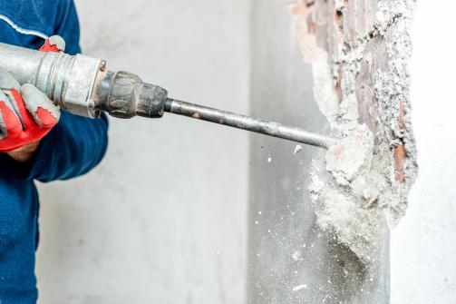 Utilisation d'un marteau perforateur pour demolir un mur